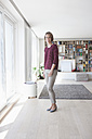 Smiling woman standing in her living room - RBF003769
