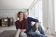 Smiling couple sitting on the floor at home watching something - RBF003778