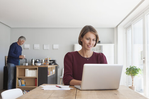 Portrait of woman using laptop at home - RBF003790