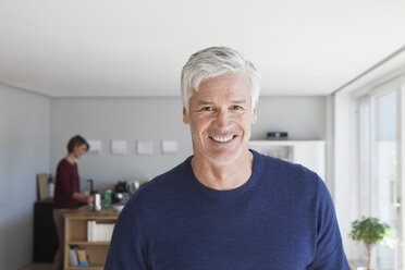 Portrait of smiling man with grey hair and stubble at home - RBF003793
