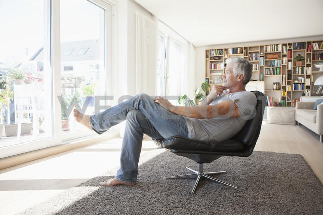 Pensive man relaxing on leather chair at home looking through the window - RBF003799