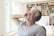 Portrait of relaxed man hearing music with headphones at home - RBF003802