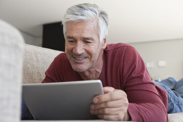 Portrait of smiling man lying on the couch at home using digital tablet - RBF003811