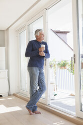 Smiling man leaning against balcony door looking at distance - RBF003817