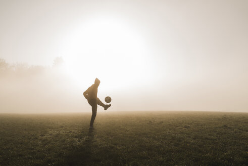Young man playing soccer on meadow in the evening - UUF006215
