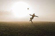 Young man playing soccer on meadow in the evening - UUF006218