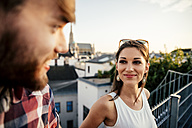 Austria, Vienna, portrait of smiling young woman face to face with her boyfriend on a roof terrace - AIF000133