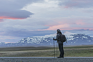 Iceland, Man standing on road looking at volcanos - PAF001520