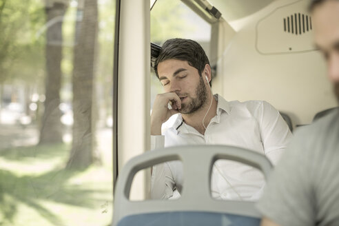 Young man sleeping in city bus - ZEF007755