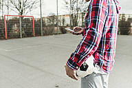 Young football player with smartphone - UUF006302
