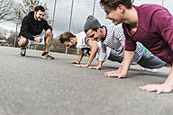 Young man motivating his friends, pushups - UUF006314