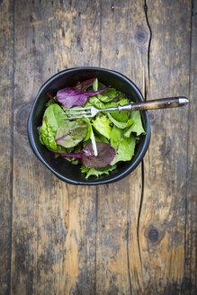 Bowl of organic mixed salad on dark wood - LVF004361