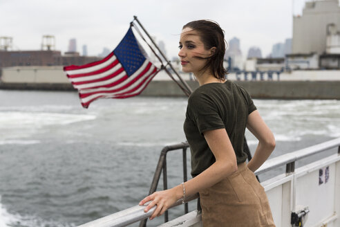 USA, New York City, young woman standing on an excursion boat on a windy day - GIOF000619