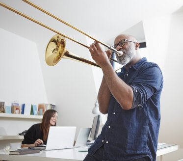 Man playing trombone at home office - RHF001148