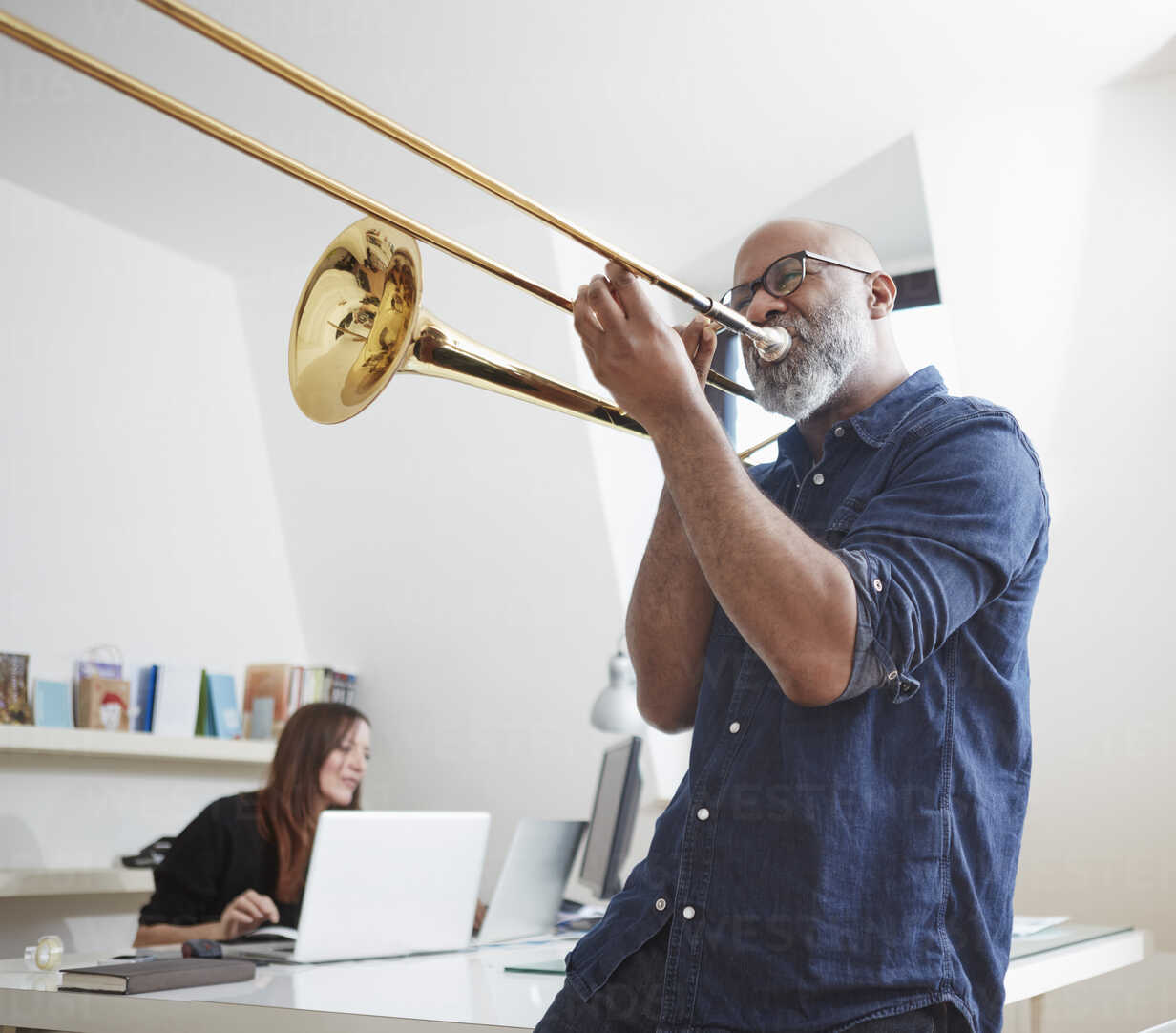 Man playing trombone at home office - RHF001148 - Rainer Holz/Westend61