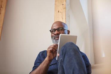 Portrait of smiling man with digital tablet - RHF001151
