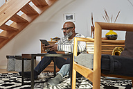 Man sitting on the floor of his living room using digital tablet - RHF001160