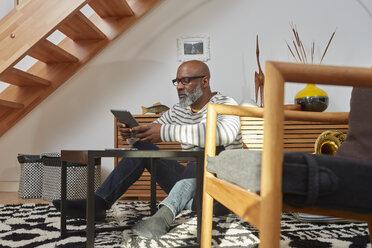 Man sitting on the floor of his living room using digital tablet - RHF001160