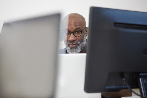 Portrait of astonished man between computer monitors - RHF001163
