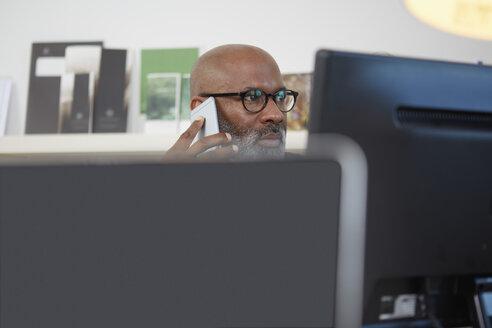Portrait of man sitting behind  computer monitors telephoning - RHF001166