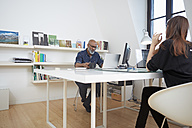 Two people working at desk in an office - RHF001169
