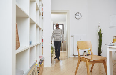 Man carrying his laptop in the kitchen - RHF001172