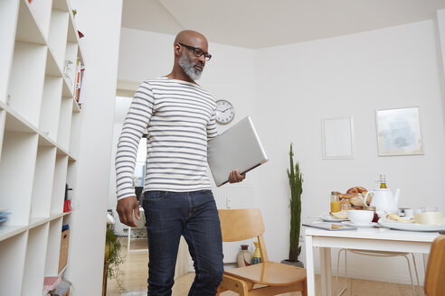 Man with laptop in his kitchen at home - RHF001175
