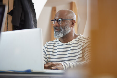 Portrait of man sitting at desk of  home office with his laptop - RHF001181