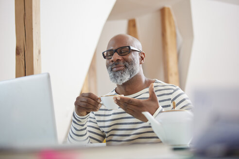 Portrait of smiling man with closed eyes sitting at his desk with cup of tea - RHF001184