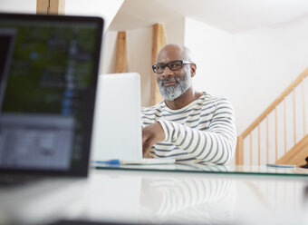 Portrait of smiling man sitting at his desk with laptop - RHF001187