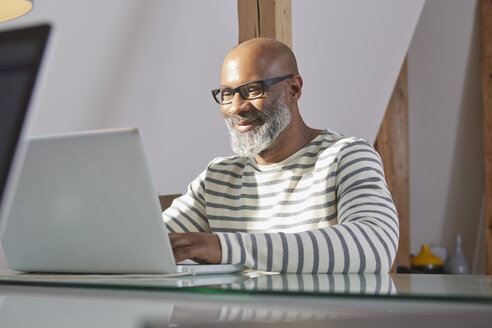 Portrait  of smiling man sitting at his desk working with laptop - RHF001190