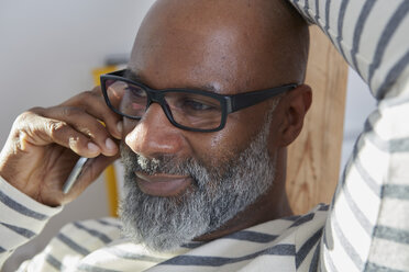 Portrait of bald man with grey beard telephoning with smartphone - RHF001193