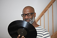 Portrait of smiling man with record - RHF001205