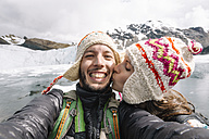 Peru, couple wearing wool chullos and kissing - GEMF000584