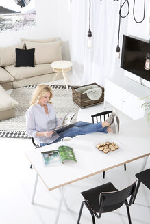 Woman sitting with feet up on the table in her living room watching magazine - MAEF011214