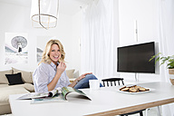 Portrait of smiling woman sitting at the table in her living room with magazines and cookies - MAEF011217