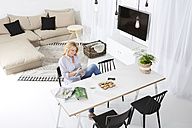 Smiling woman sitting at the table in her living room using digital tablet - MAEF011223