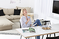 Laughing woman sitting at the table in her living room with magazine - MAEF011226
