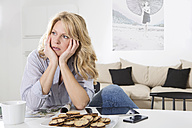 Woman sitting at the table in her living room with hands in her head - MAEF011229