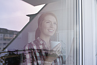 Portrait of smiling young woman with cup of coffee looking through window - RBF003834