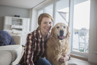 Portrait of smiling young woman with her dog at home - RBF003843