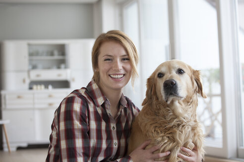 Portrait of smiling young woman with her dog - RBF003846