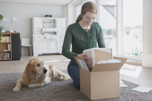 Smiling young woman kneeling on the floor beside her dog unpacking a parcel - RBF003870