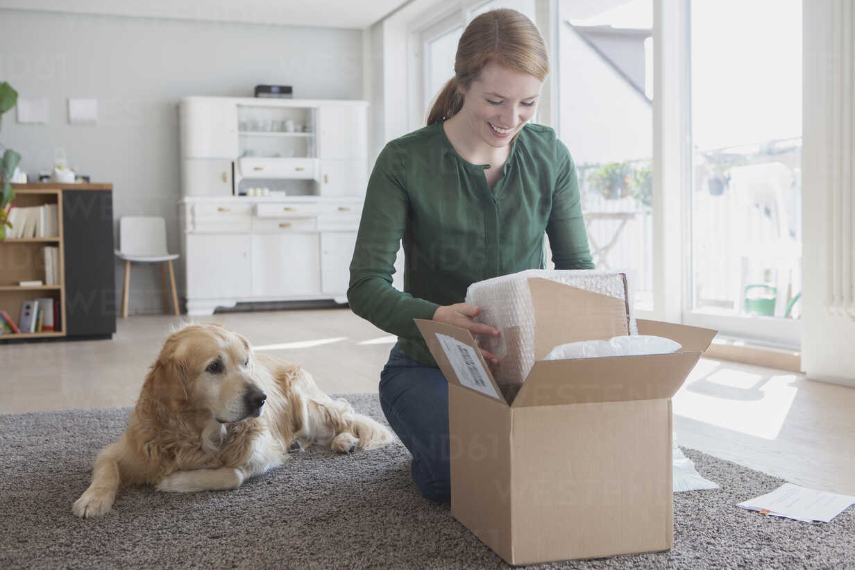 Smiling young woman kneeling on the floor beside her dog unpacking a parcel - RBF003870 - Rainer Berg/Westend61