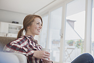 Smiling young woman relaxing with cup of coffee at home - RBF003888