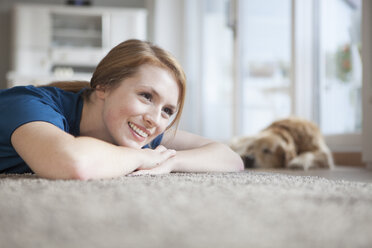 Portrait of smiling young woman relaxing on the floor at home - RBF003906