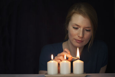 Portrait of young woman lighting candles - RBF003909