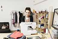 Young fashion designer working in her studio - JRFF000269