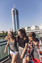 Austria, Vienna, three happy teenagers walking on a bridge in front of the Millenium Tower - AIF000148