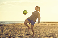 Spain, Young woman playing soccer at the beach - KIJF000081